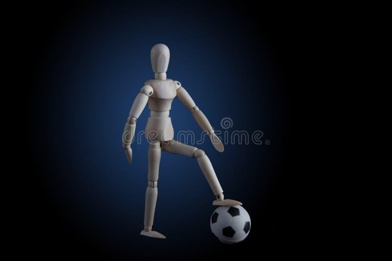 Drewniany figurki kroczenie na piłki nożnej piłce na czarnym tle z fotografia stock