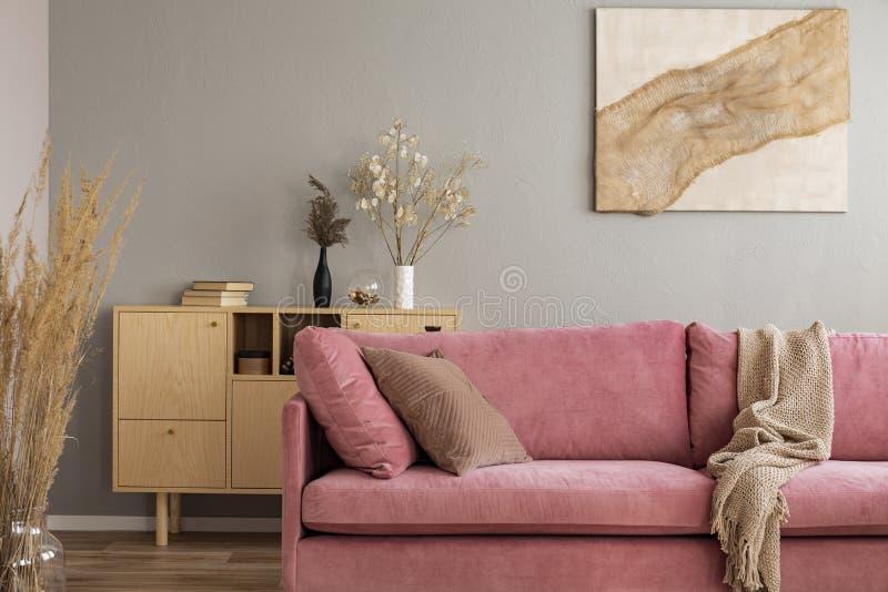 Drewniany gabineta i abstrakta obraz za różową leżanką w eleganckim żywym izbowym wnętrzu zdjęcia stock