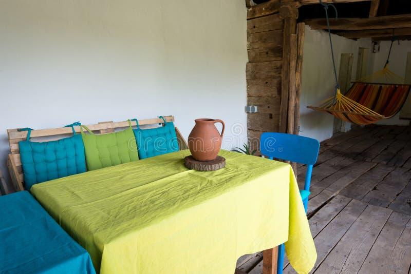 Drewniany ganeczek stary rocznika dom na wsi z stołami, krzesłami i hamakiem, - miejsce dla jeść i relaksować obraz royalty free