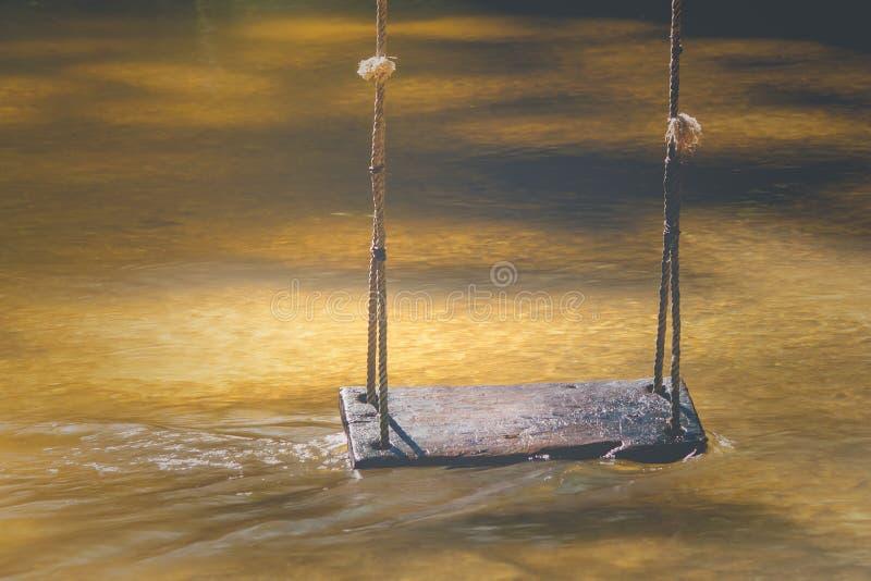 Drewniany huśtawkowy obwieszenie na drzewie nad wodny strumień przy outside kurortem w rocznika stylu miękkie ogniska, fotografia royalty free