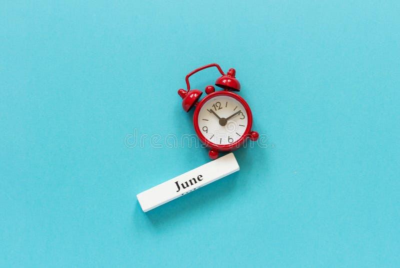 Drewniany kalendarzowy lato miesiąc Czerwiec i czerwony budzik na błękitnego papieru tle Pojęcie Czerwiec Cześć lub Do widzenia C fotografia stock