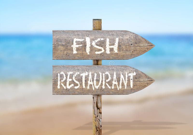 Drewniany kierunku znak z rybią restauracją obraz royalty free