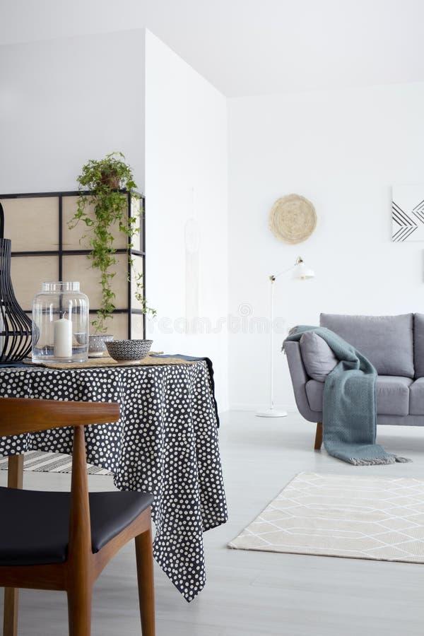 Drewniany krzesło przy łomotać stół w białym mieszkania wnętrzu z popielatą kanapą z zieloną koc Istna fotografia fotografia stock