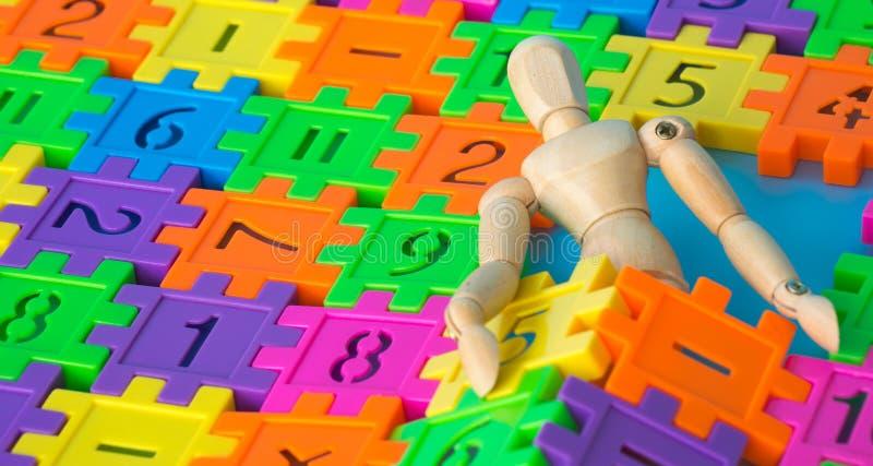 Drewniany kukiełkowy sen w kolorowej klingeryt liczbie na błękitnym tle Pojęcie edukaci obliczenie lub mathematics Kopiuje przest zdjęcie stock