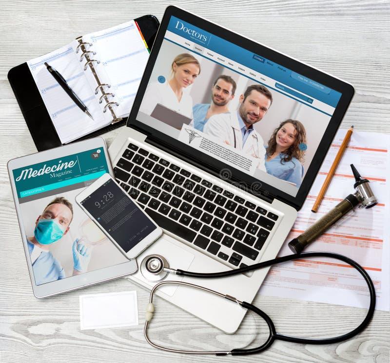 Drewniany lekarki biurko w wysokiej definici z laptopem, pastylką i mo, obraz stock