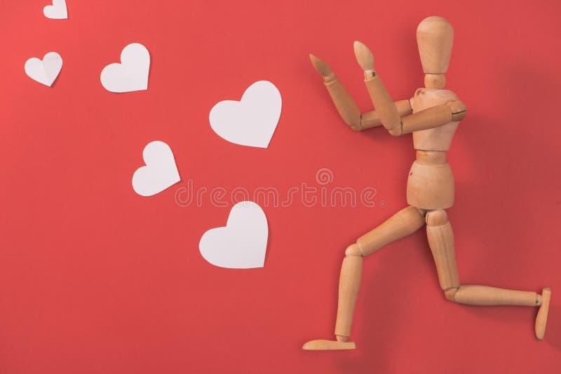 Drewniany mężczyzna postaci bieg łapać czerwonego serce fotografia royalty free