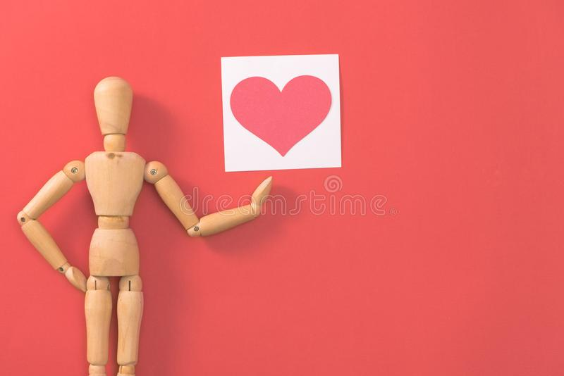 Drewniany mężczyzna postaci mienia czerwieni serce Pojęcie dla walentynki ` s dnia zdjęcia stock