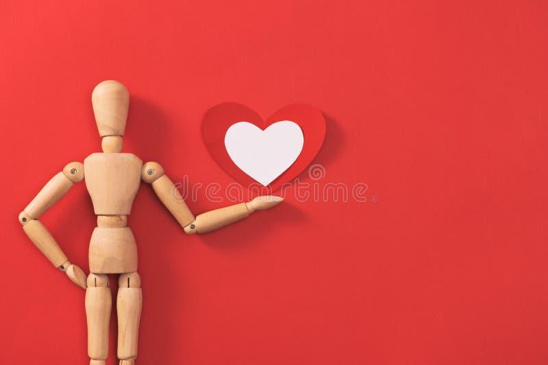 Drewniany mężczyzna postaci mienia czerwieni serce Pojęcie dla walentynki ` s dnia obraz royalty free