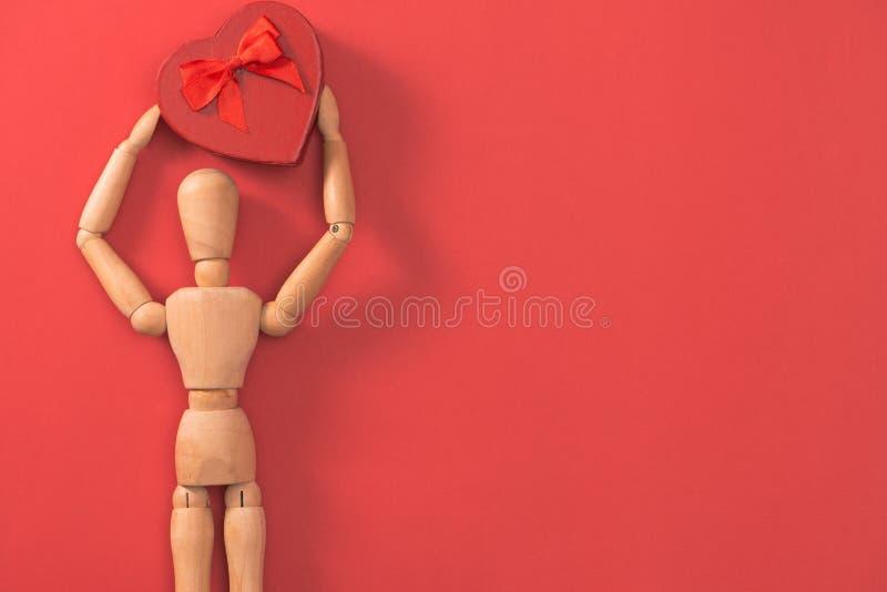 Drewniany mężczyzna postaci mienia czerwieni serce Pojęcie dla walentynki ` s dnia fotografia royalty free