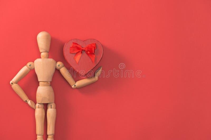 Drewniany mężczyzna postaci mienia czerwieni serce Pojęcie dla walentynki ` s dnia zdjęcia royalty free