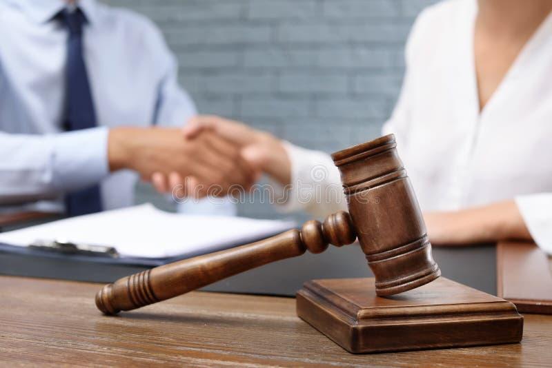 Drewniany młoteczek i zamazany prawnik z klientem obrazy stock