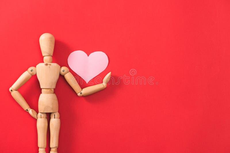Drewniany m??czyzna postaci mienia czerwieni serce Poj?cie dla walentynki ` s dnia fotografia stock