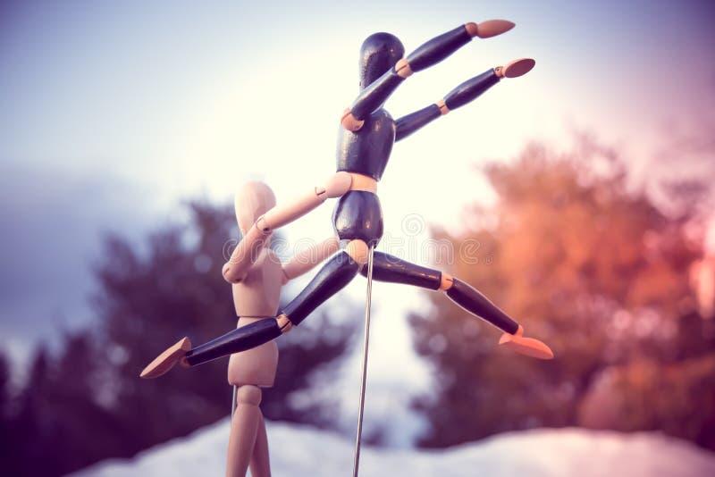 Drewniany mannequin pomaga innego mannequin skacze zdjęcie stock