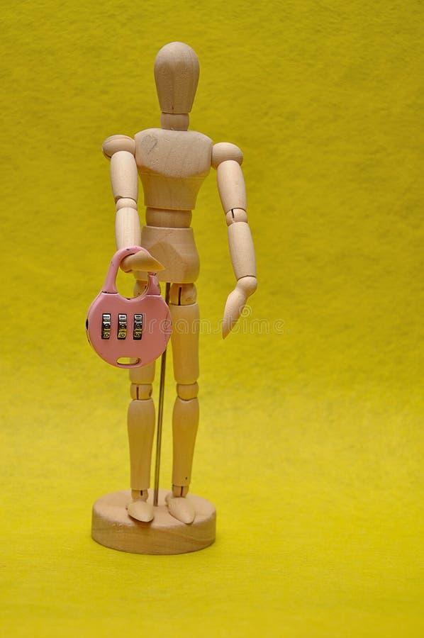 Drewniany mannequin trzyma kombinacji kłódkę zdjęcie stock