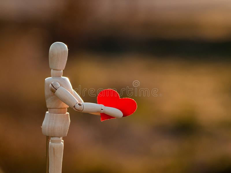 Drewniany mannequin z czerwonym sercem na jego wręcza pojęcie romantyka i miłość zdjęcie royalty free