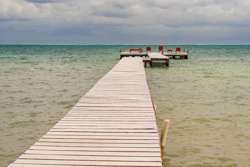 Drewniany molo dok, widok na ocean przy Caye doszczelniaczem Belize Karaiby i zdjęcia stock