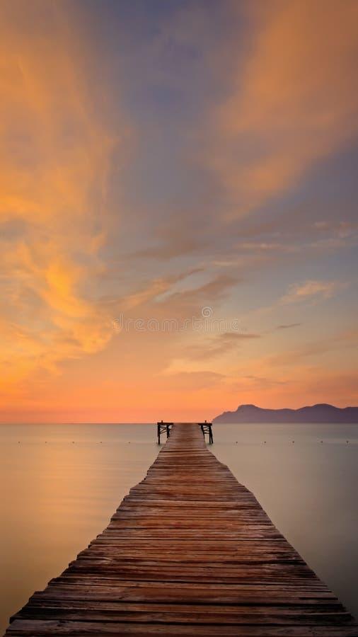 Drewniany molo, jetty/, playa de Muro, Alcudia, wschód słońca, góry, odosabnialiśmy plażowego, złotego światło słoneczne, odbicie obrazy stock