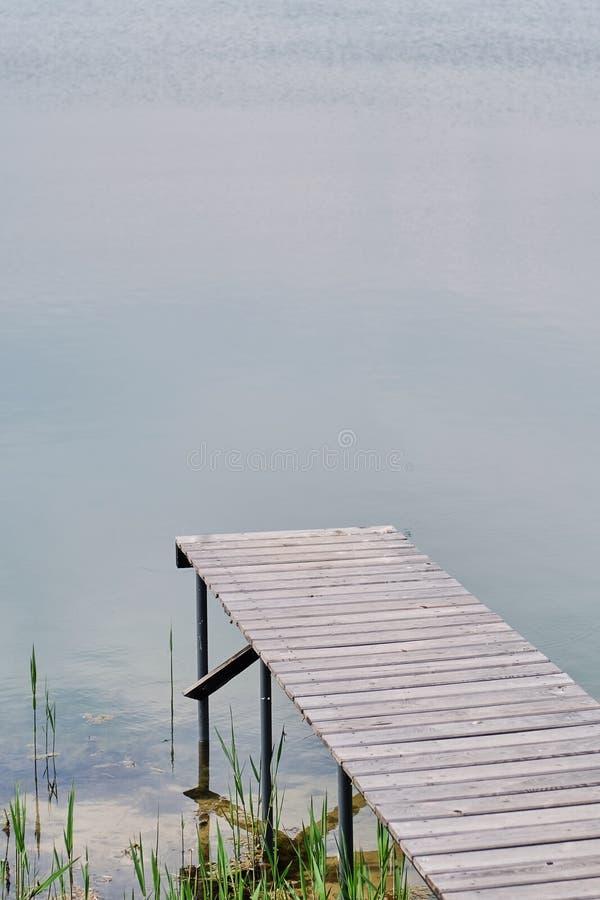 Drewniany molo lub jetty na błękitnej jeziornej odbicie wodzie zmierzchu i nieba zdjęcie royalty free