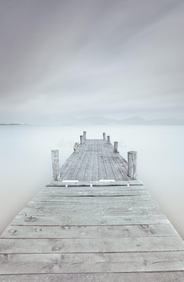 Drewniany molo na jeziorze w chmurnym i mgłowym nastroju. zdjęcie stock