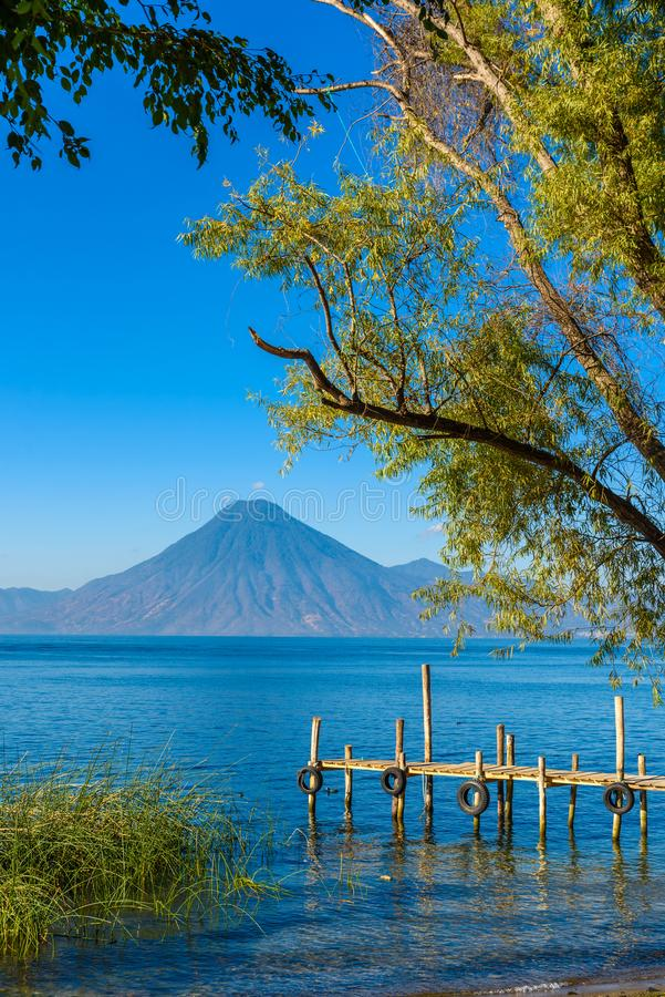Drewniany molo przy Jeziornym Atitlan na brzeg przy Panajachel, Gwatemala Z piękną krajobrazową scenerią volcanoes Toliman, Atitl zdjęcie stock