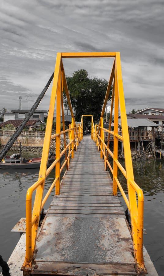 Drewniany most nad kanałem stalowy budynek malował kolor żółtego zdjęcie royalty free
