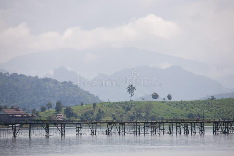 Drewniany most przez przez rzeki z halnym tłem zdjęcia royalty free