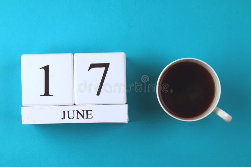 Drewniany notatnik z datą na Czerwu 17 i kawowym kubkiem na błękitnym pastelowym tle Ojciec, s dzień ' zdjęcia stock