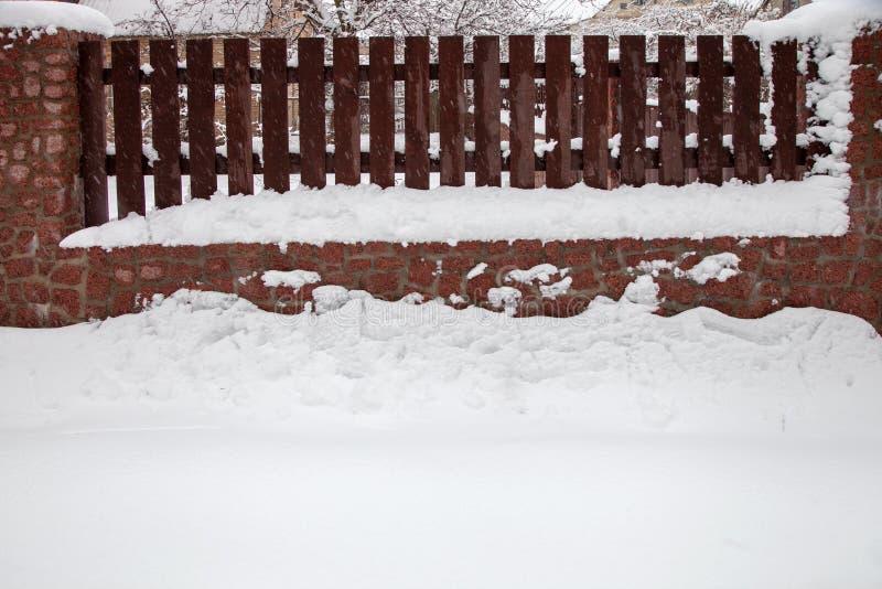 Drewniany ogrodzenie z kamienną podstawą zakrywającą w śniegu zdjęcia royalty free