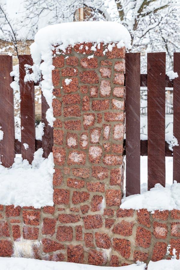 Drewniany ogrodzenie z kamienną podstawą zakrywającą w śniegu zdjęcia stock