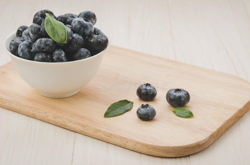 drewniany poparcie biały puchar z świeżym blueberry/on drewniany poparcie biały puchar z świeżą czarną jagodą kosmos kopii obrazy royalty free