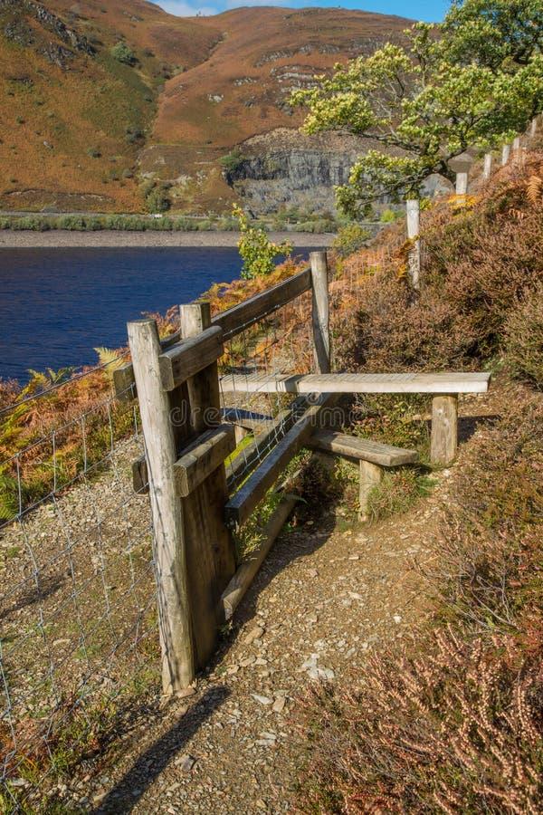 Drewniany przełazu styl nad ogrodzeniem, z bracken Jezioro i góra zdjęcie royalty free