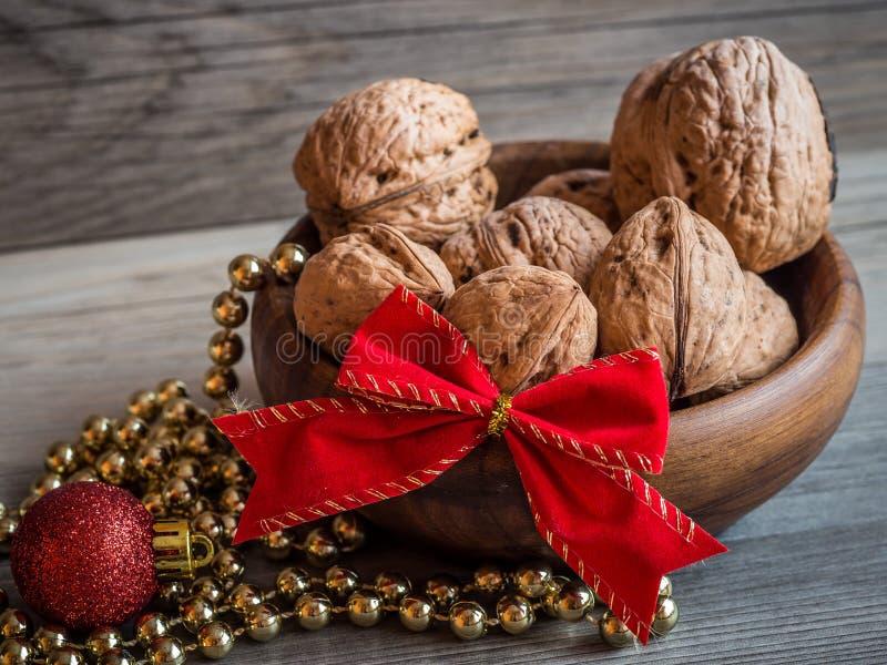 Drewniany puchar pełno orzechy włoscy, czerwony łęk, złocisty ornament i złoty boże narodzenie łańcuch, zdjęcia stock