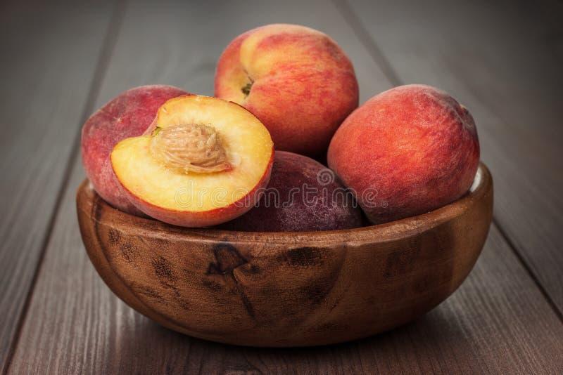 Drewniany puchar z niektóre brzoskwiniami na stole zdjęcie royalty free