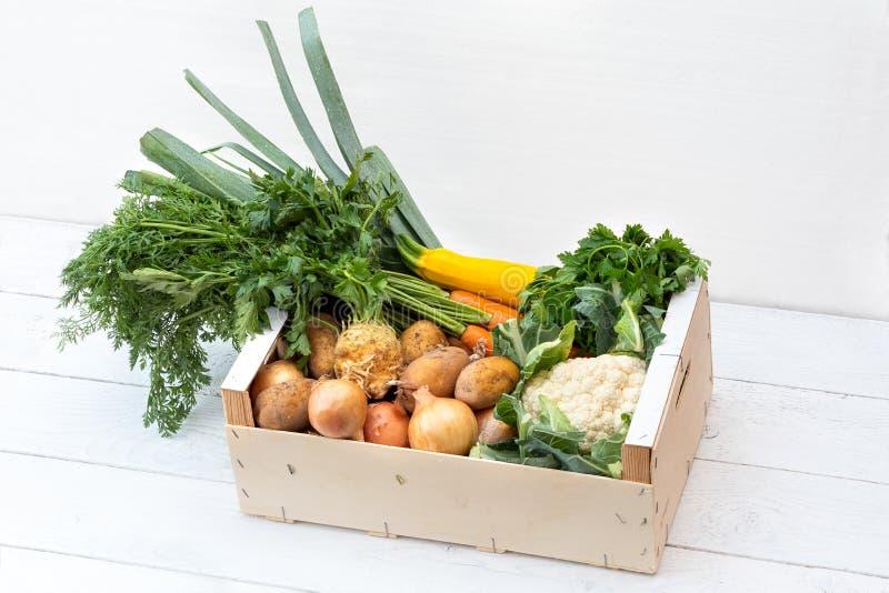 Drewniany pudełko świezi warzywa od rolników wprowadzać na rynek na biel malującym drewno stole zdjęcie stock