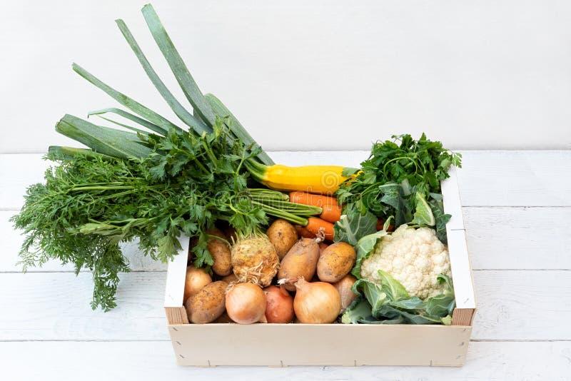 Drewniany pudełko świezi warzywa od rolników wprowadzać na rynek na biel malującym drewno stole zdjęcia royalty free