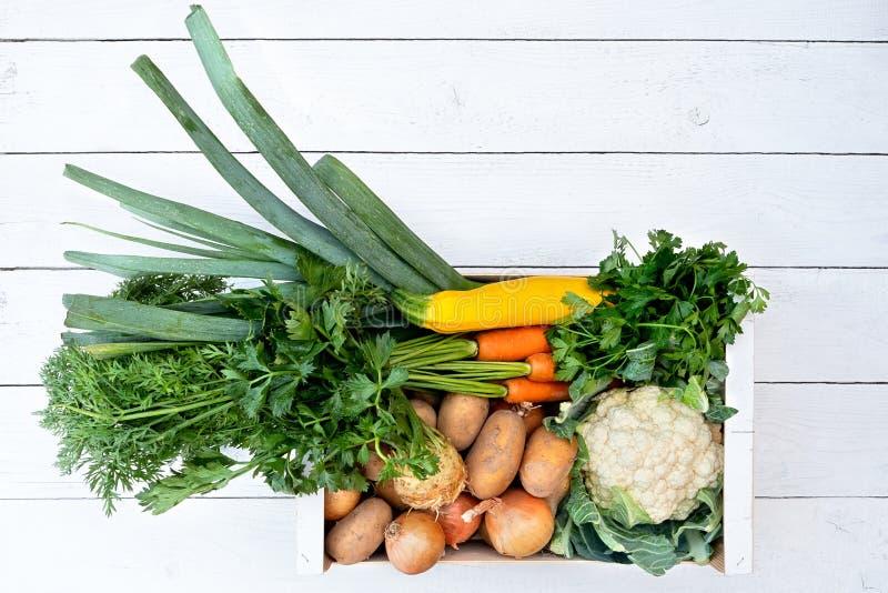 Drewniany pudełko świezi warzywa od rolników wprowadzać na rynek na biel malującym drewno stole z góry Przestrze? dla teksta fotografia stock