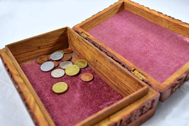 Drewniany pudełko z czerwonym chodnikiem i monetami fotografia royalty free