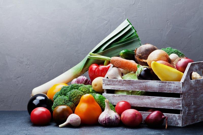 Drewniany pudełko z jesieni żniwa gospodarstwa rolnego warzywami i korzeniowymi uprawami na ciemnym kuchennym stole Zdrowy i żywn zdjęcie royalty free
