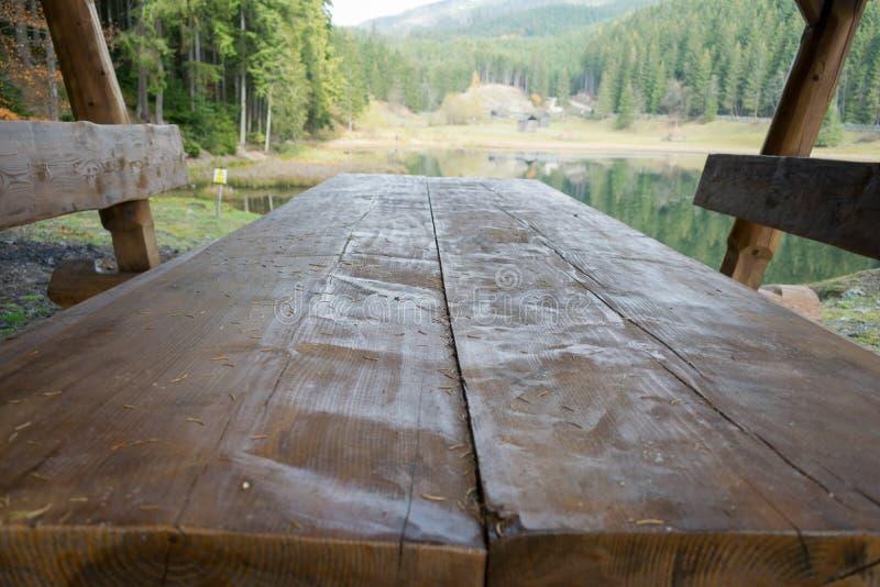 Drewniany pykniczny stół jeziorem fotografia stock