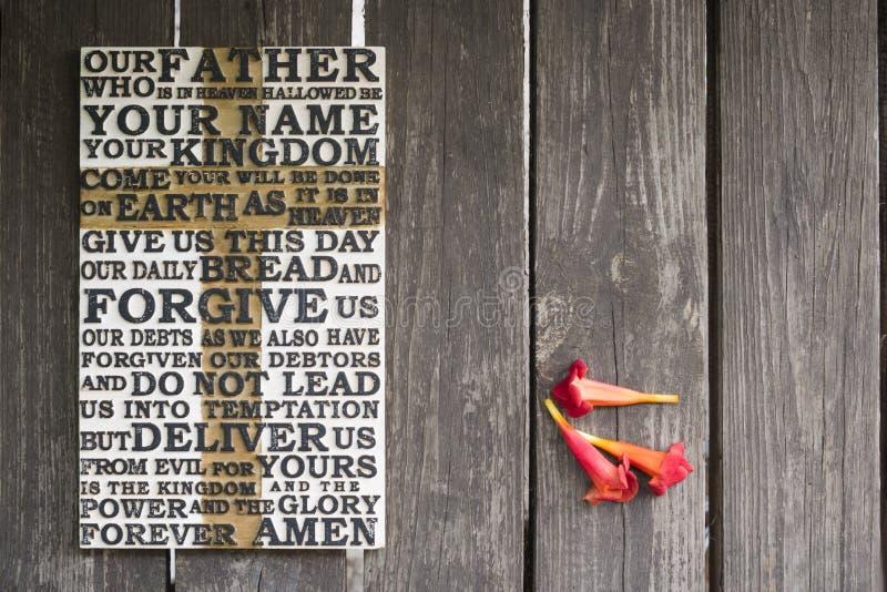 Drewniany rzeźbiący słowo władyki ` s modlitwa na podławej drewnianej desce z czerwonymi kwiatami zdjęcie stock