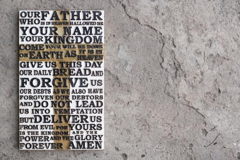 Drewniany rzeźbiący słowo władyki ` s modlitwa na popielatym betonowym tle obrazy royalty free