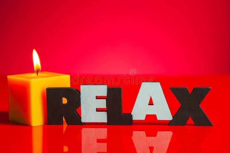 Drewniany słowo 'Relaksuje' z płonącą świeczką zdjęcie stock