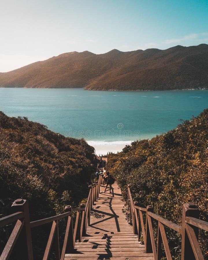 Drewniany schody most który prowadzi puszek piękna piaskowata plaża z ludźmi na mnie fotografia royalty free