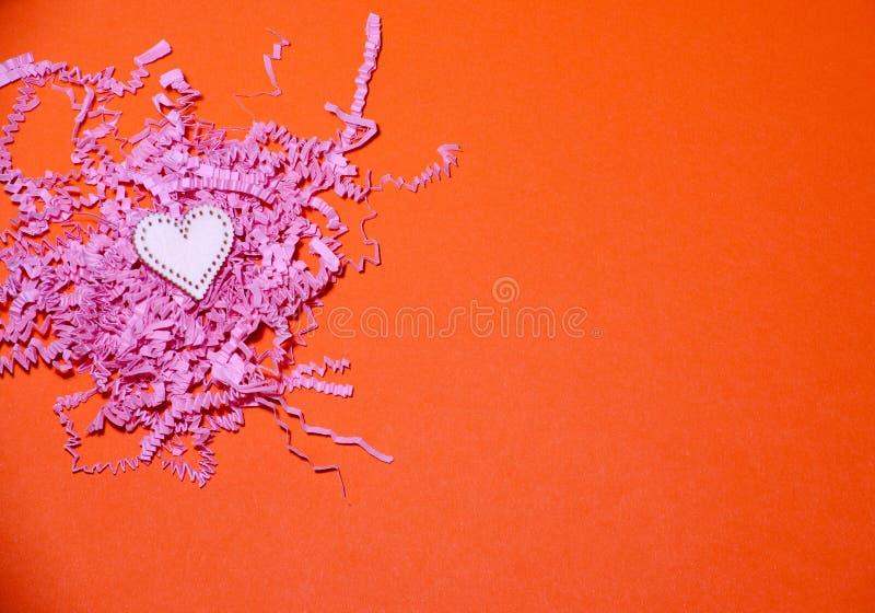 Drewniany serce na pomarańczowym papierowym tle z menchia pokrajać papierem Walentynka dnia tło z handmade zabawkarskimi sercami obrazy royalty free