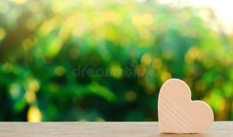 Drewniany serce na zielonym bokeh tle Pojęcie miłość i romans serce odizolowane kształtu white pomidorowego Organowa darowizna Zw obrazy stock