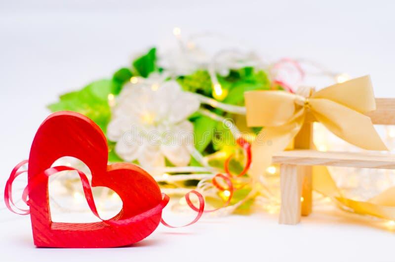 Drewniany serce z łękiem na ławce na białym tle czerwona róża pojęcie miłość, romantyczny wystrój obraz royalty free