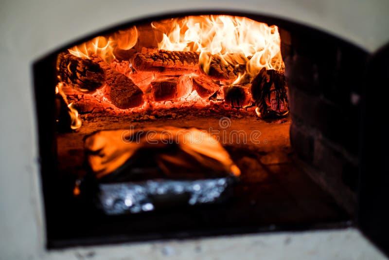 drewniany skraju piekarnik z ogieniem przy swój szczytem, naczynie w folii inside obraz royalty free