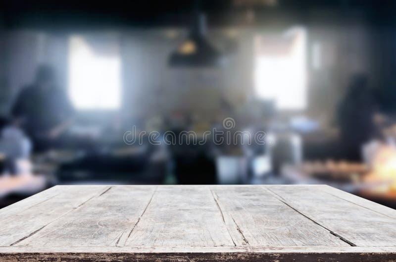 Drewniany stół na abstrakt zamazującej kuchni z szefa kuchni kucharstwem w restauracyjnym tle i przestrzeń dla dekoracja pokazu zdjęcia royalty free