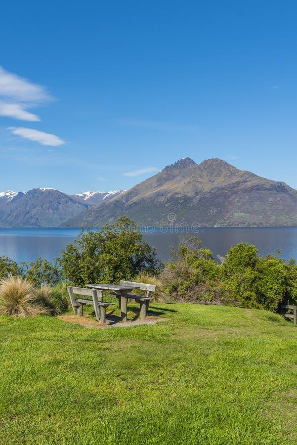 Drewniany stół i ławka przeciw tłu jeziorny Wakatipu, Queenstown, Nowa Zelandia pionowo obraz royalty free