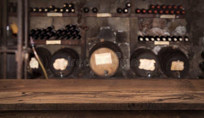 Drewniany st?? na rozmytym tle wino butelki i bary?ki obrazy stock